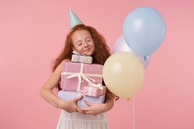 長い巻き毛のポジティブな素敵な赤毛の女性の子供は休日を祝い、ピンクの上に立っている間真のポジティブな感情を表現します。子供とお祝いのコンセプト 無料写真