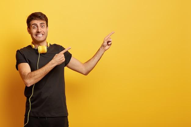 긍정적 인 남성 모델은 치아를 움켜 쥐고 텍스트 또는 광고의 빈 공간을 가리키며 목에 헤드폰을 착용합니다. 무료 사진