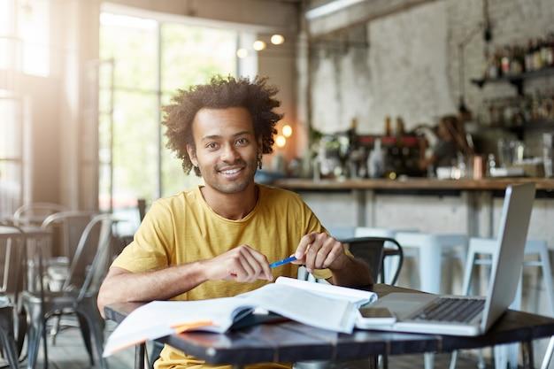 Позитивный мужчина сидит за столом в кафе, используя ноутбук Бесплатные Фотографии