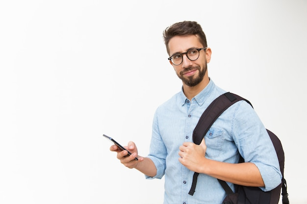 Positive male tourist with backpack using mobile phone Free Photo