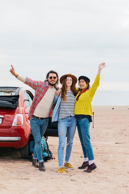 Positive man and cheerful women embracing near car on sea coast Free Photo