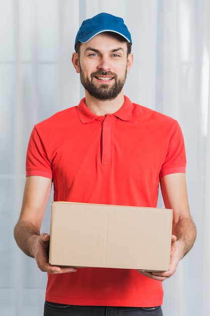 Positive man delivering parcel Free Photo