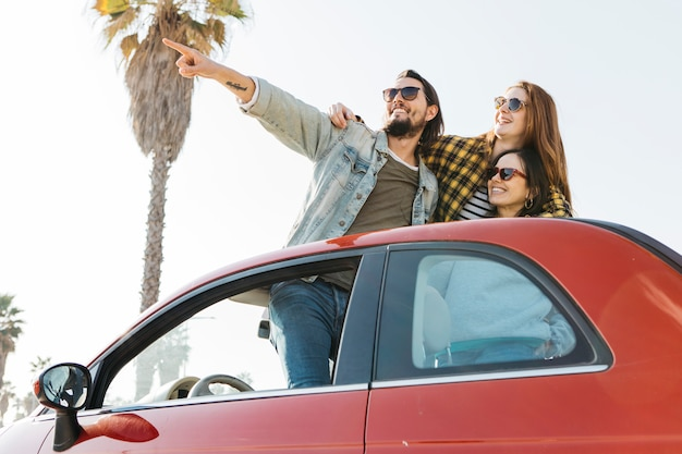 Positive man pointing near smiling women leaning out from auto Free Photo