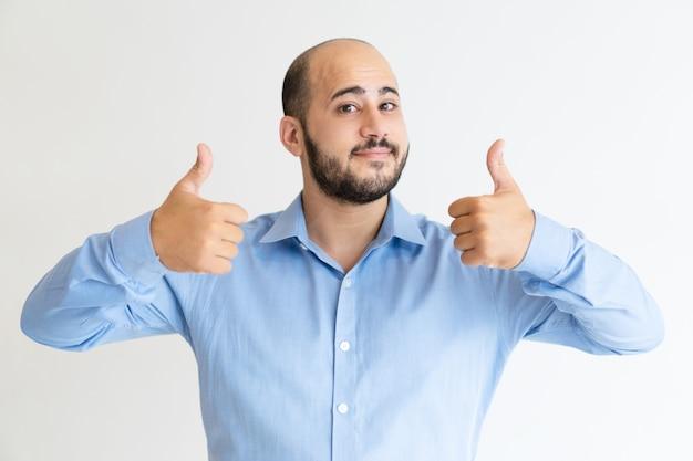 Positive man showing both thumbs up and looking at camera   Free Photo