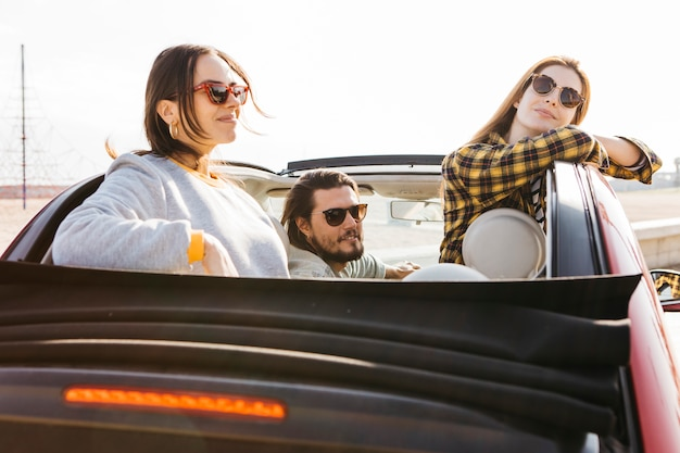 Positive man sitting in car near smiling women leaning out from auto Free Photo