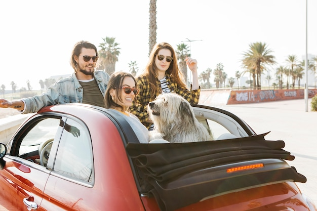 Positive man and smiling women near dog leaning out from auto Free Photo
