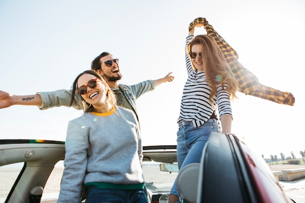 Positive man and smiling women with skirt in hand having fun and leaning out from car Free Photo