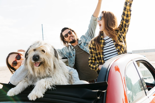 Positive man and smiling women with upped hands near dog leaning out from auto Free Photo