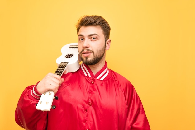 彼の手にウクレレを付けて黄色の上に立っているひげを持つ正男 Premium写真