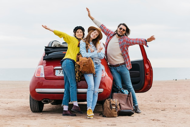 Positive man with upped hands near embracing women and car on sea beach Free Photo