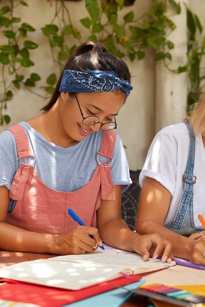 ポジティブな混血の女性は、ヘッドバンド、ピンクのサラファン、透明な眼鏡をかけ、クラスメートが近くに座っている日記にメモを書き、居心地の良いカフェのインテリアでポーズをとります。アサイン女性未来デザイナーがコースワークを準備 無料写真