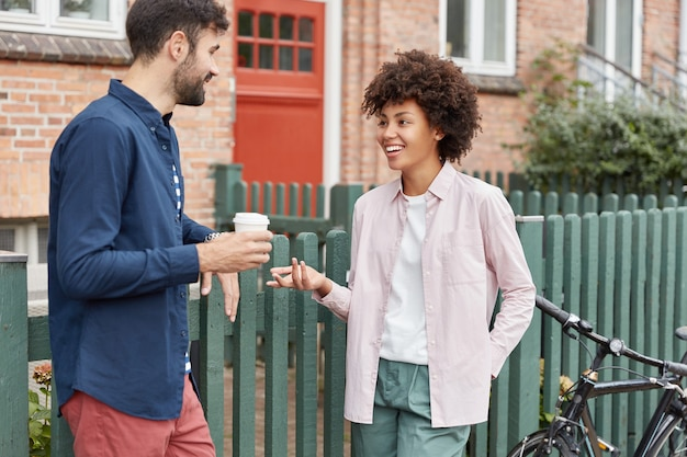 Positive multiracial couple walk in rural setting, stroll during weekends, drink takeaway coffee, stand near fence, have pleasant talk with each other Free Photo