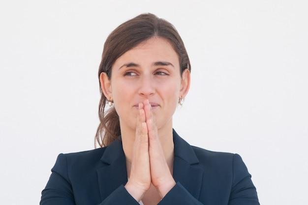 Positive office worker praying for luck Free Photo