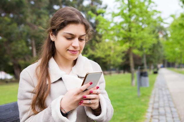 Positive peaceful girl texting message Free Photo