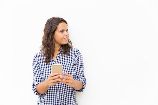 Позитивная задумчивая латинская женщина с мобильным телефоном Бесплатные Фотографии