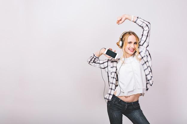 Позитивное фото эмоциональная милая девушка со смартфоном, наслаждается своей жизнью, слушает любимую музыку, танцует на серой стене. концепция отдыха и технологий. хорошее настроение. Бесплатные Фотографии