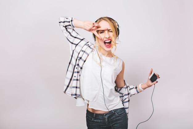 大きなヘッドフォンで音楽を聴くカジュアルな服装でブロンドの髪を持つうれしそうなエネルギー少女の肯定的な肖像画。彼女は踊っていて、スマートフォンを持っています。分離されました。 無料写真