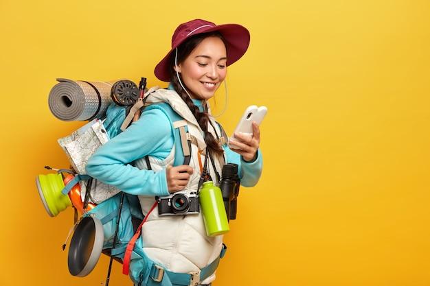 Il turista abbastanza asiatico positivo utilizza gadget moderni per la navigazione, vestito con cappello e maglione con giacca, usa binocolo, fotocamera retrò, karemat durante il viaggio si trova contro il muro giallo Foto Gratuite