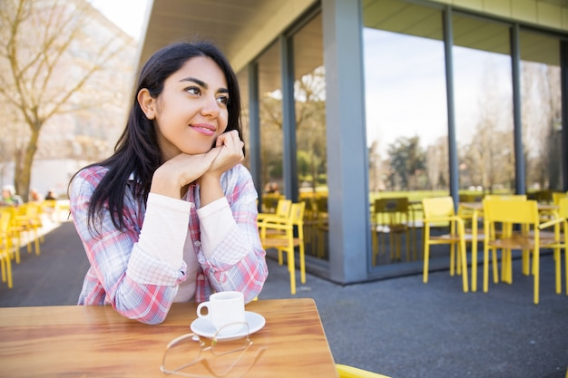 Positive pretty young lady enjoying drinking coffee in cafe Free Photo