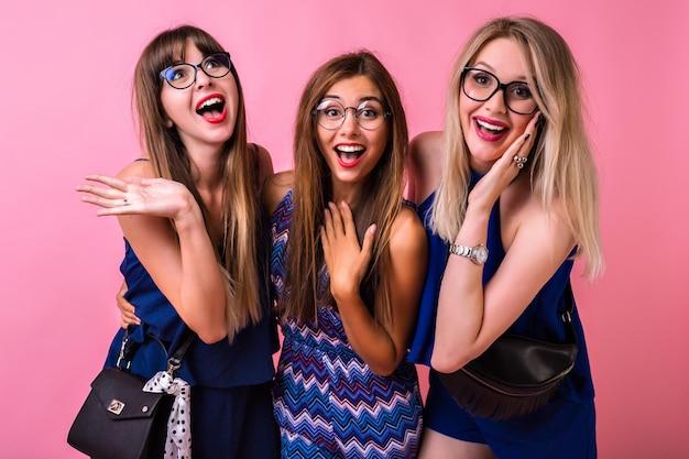 Концепция дружбы «позитивные отношения», три веселые симпатичные женщины вместе веселятся, обнимаются и удивляются эмоциям, сочетающиеся по цвету вечерние наряды и аксессуары, милые смайлы, время для групповой вечеринки. Бесплатные Фотографии