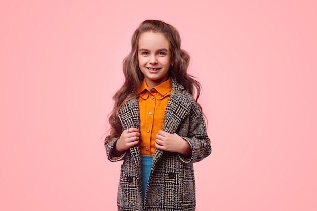 ピンクの背景に子供のためのファッションを表現しながら、カジュアルな服と暖かい市松模様のコートの笑顔とカメラを見ているポジティブな女子高生 Premium写真
