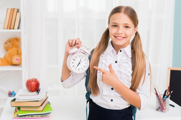 Positive schoolgirl pointing at clock Free Photo