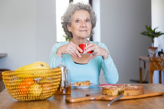 Positive senior lady enjoying tasty pie Free Photo