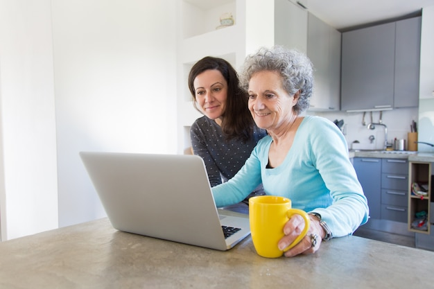 Positive senior lady showing photos to daughter on laptop Free Photo