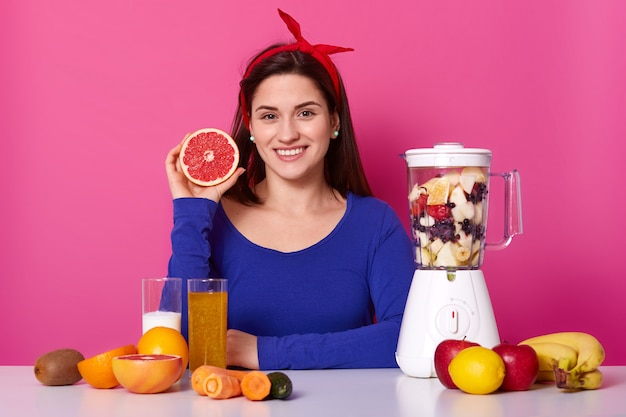 Positive woman in blue jumper and headband, prepares healthy juice, uses fresh ingredients, adds cut fruits in blender jar, holds slice of grapefruit likes smoothie in morning. vegeterian food concept Free Photo