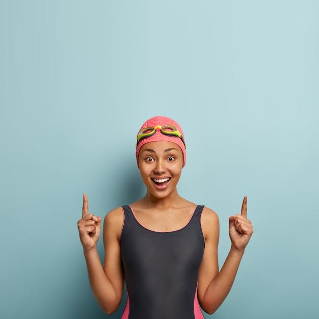 ポジティブな女性は、黒い水着、水泳帽、ゴーグルを身に着けたウォータースポーツを楽しんでいます。上の空きスペースをポイントし、ダイビング用のアクセサリーを宣伝し、コンテストの準備をしています。スポーツとプロモーションのコンセプト 無料写真