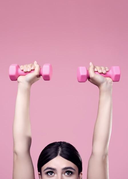 Позитивная женщина, тренирующаяся с гантелями Бесплатные Фотографии
