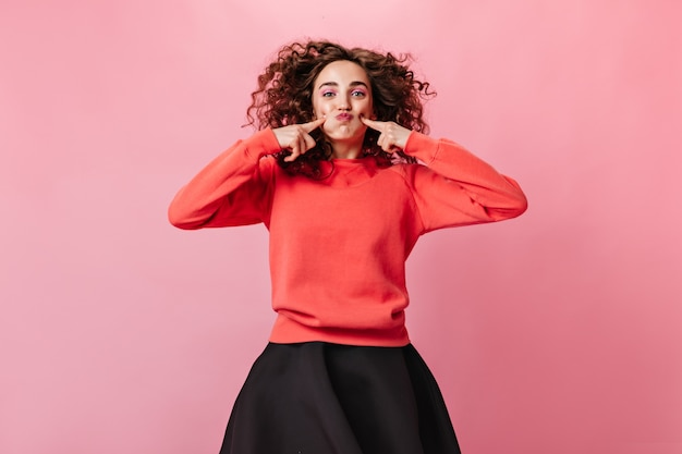オレンジ色のスウェットシャツのポジティブな女性はピンクの背景に変な顔をします 無料写真