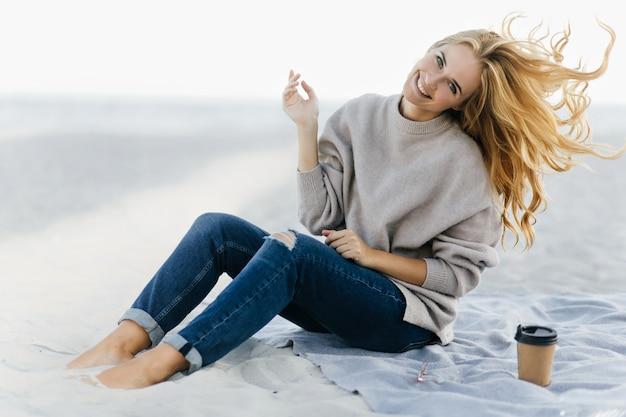 Позитивная женщина в мягком свитере дурачится на пляже. открытый портрет очаровательной женской модели, сидящей в песке с чашкой чая. Бесплатные Фотографии
