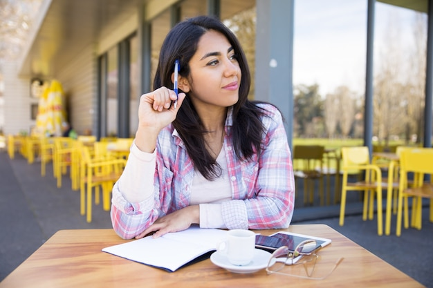 Positive woman making notes in outdoor cafe Free Photo