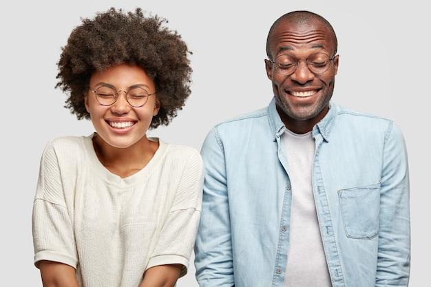 L'uomo e la donna positivi hanno espressioni compiaciute, rallegrandosi delle buone notizie Foto Gratuite