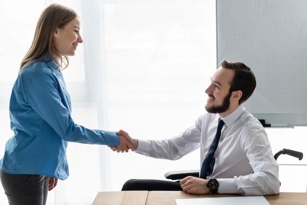 Donna e uomo positivi che stringono insieme le mani Foto Gratuite
