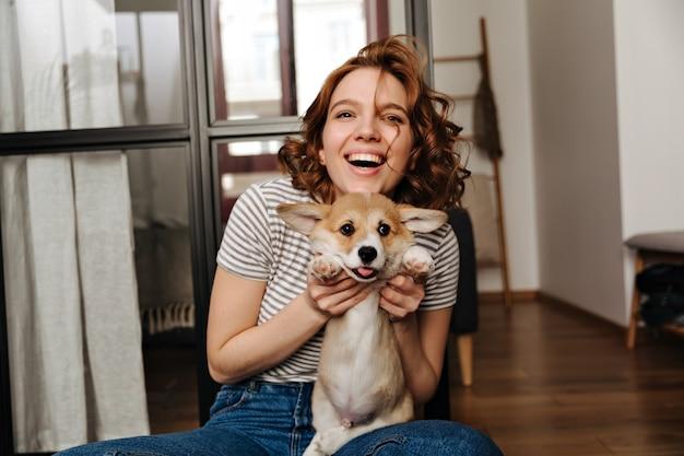 긍정적 인 여자는 거실 바닥에 앉아 미소로 그녀의 사랑하는 강아지와 함께 재생됩니다. 무료 사진