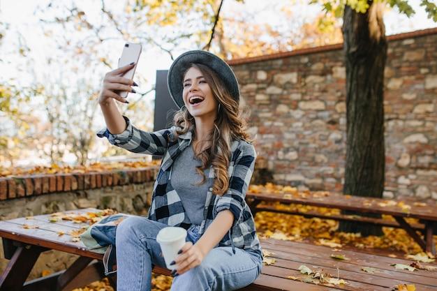 秋の公園でコーヒーを飲みながら自分撮りを作る薄茶色の髪のポジティブな女性 無料写真
