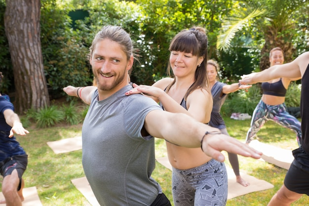 Positive yoga trainer helping trainee Free Photo