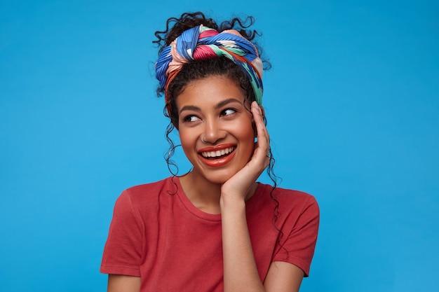 ポジティブな若い魅力的なブルネットの巻き毛の女性は、青い壁の上でポーズをとって、心地よい笑顔で脇を見ながら、上げられた手で彼女のあごを傾けてマルチカラーのヘッドバンドを持っています 無料写真