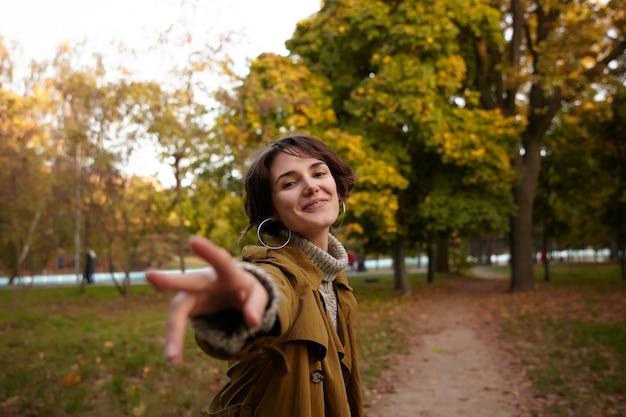 Positiva giovane signora bruna attraente con acconciatura casual sorridente piacevolmente e allungando la mano alzata, camminando su alberi ingialliti nel parco cittadino Foto Gratuite