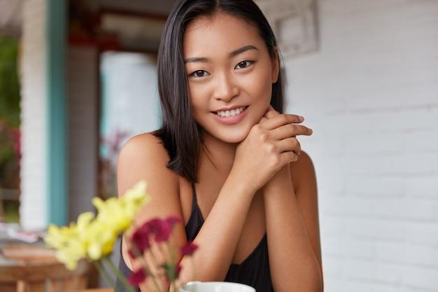 Позитивная молодая красивая азиатка с широкой теплой улыбкой, с темными волосами и здоровой кожей, довольна полноценным отдыхом и обслуживанием в ресторане. естественная красота Бесплатные Фотографии