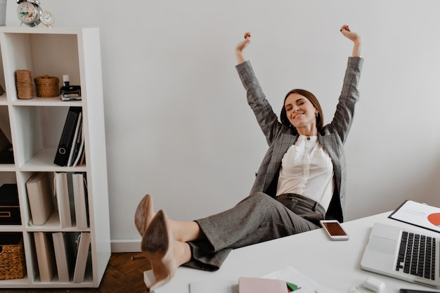 Positive young business lady leans back in her chair and raises her arms up with satisfaction against shelves of documents. Free Photo