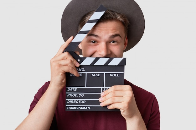Positive young cameraman holds clapboard near face, has joyful expression, wears hat, prepares for making cutaway, involved in filming, poses on white studio wall. cinematography concept Free Photo