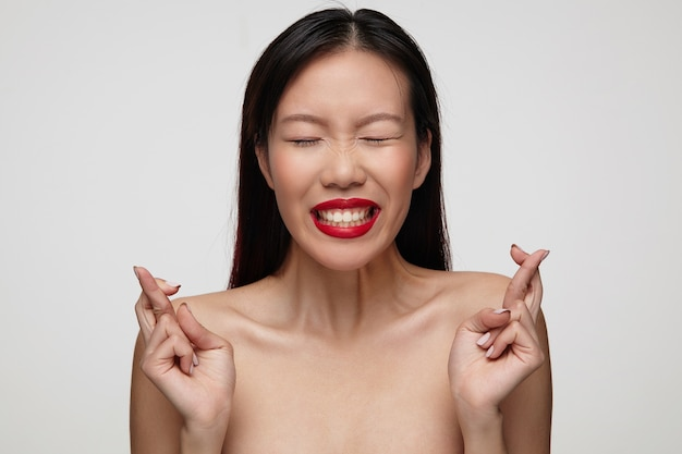 Positive young charming dark haired woman with festive makeup raising hands with crossed fingers and keeping her eyes closed while making wish, posing over white wall Free Photo