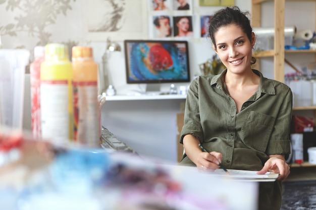 긍정적 인 젊은 창조적 인 여자 부담없이 옷을 입고, 그녀의 워크샵에 앉아, 연필로 스케치를 만들고, 창작 과정에 참여하고, 그녀의 작품을 즐기는. 사람, 라이프 스타일 및 예술 개념 무료 사진