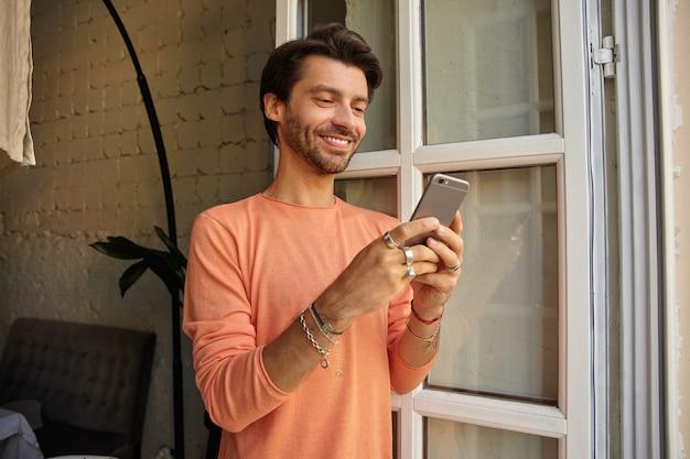 開いた窓に寄りかかって、携帯電話を手に持って、広い笑顔で画面を見ている桃色のセーターの肯定的な若い黒髪の男性 無料写真