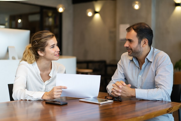 Positive young employee showing report to business colleague Free Photo