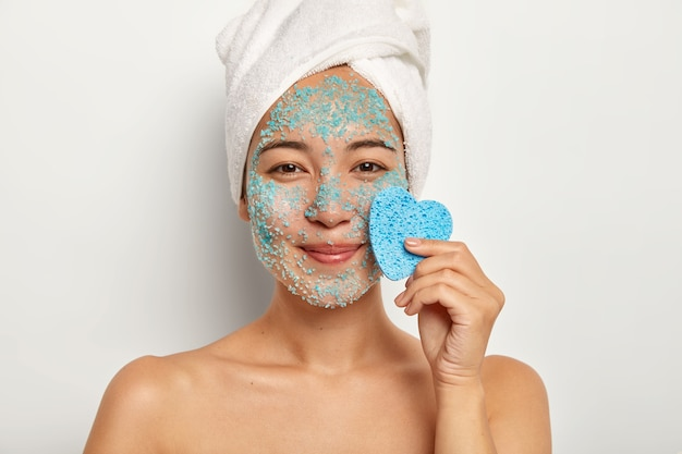Positive young female model with pleasant smile, applies natural scrub on face, stands with naked body, keeps blue sponge near face, looks happily Free Photo