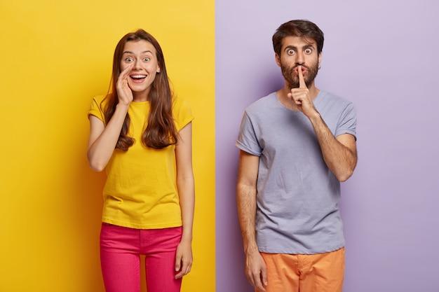 La giovane femmina positiva sussurra il segreto con l'espressione felice, il ragazzo serio tiene l'indice sulle labbra Foto Gratuite